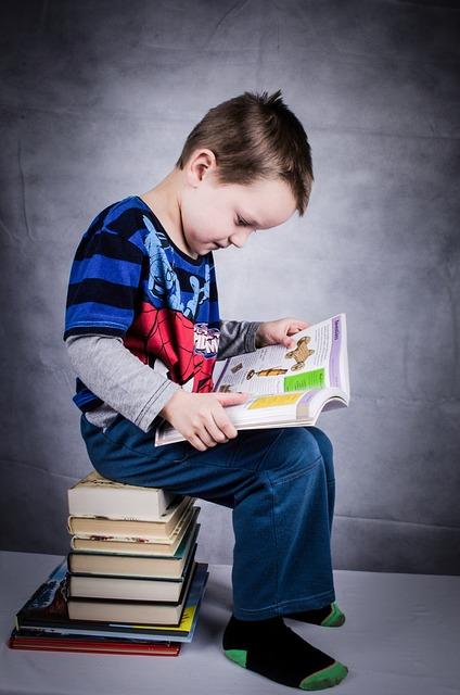 bambino seduto che legge un libro