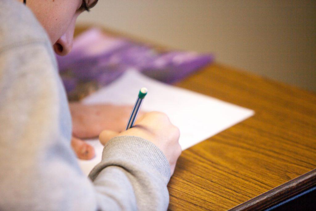 ragazzo che scrive seduto in classe